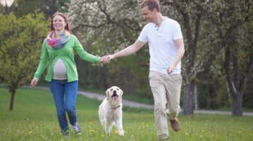 pregnant-woman-and-man-walking-dog
